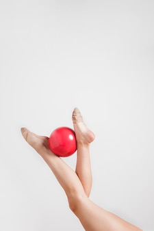 Rythmic gymnast posing with the ball