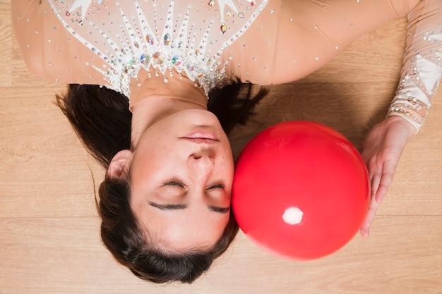 Rythmic gymnast posing with the ball