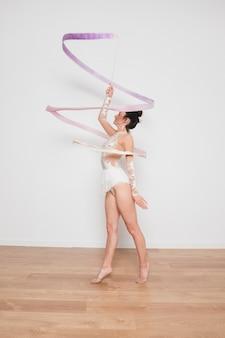 Ритмичная гимнастка позирует с лентой