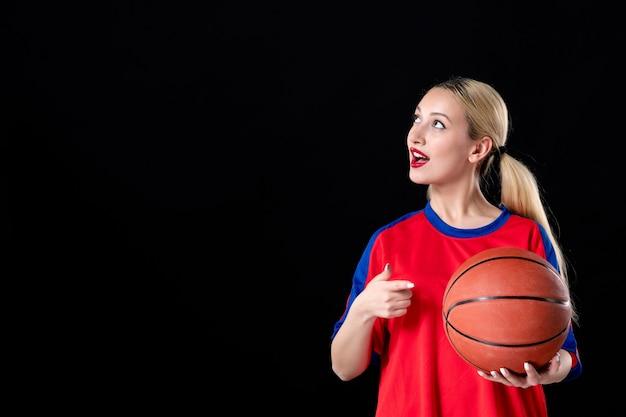 Баскетболистка с мячом на темном изолированном фоне спортсмены играют в игру действие