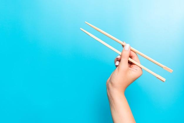 青に女性の手で保持されている木製の箸。空のスペースでsを食べる準備ができて