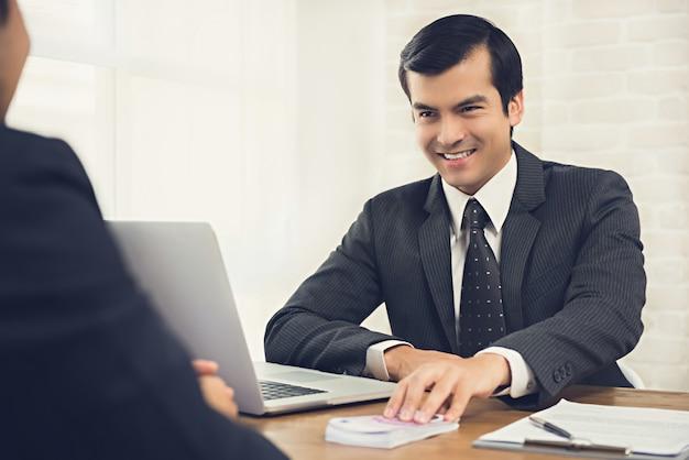 作業テーブルで彼のパートナーにお金を与えるsなトリッキーなビジネスマン