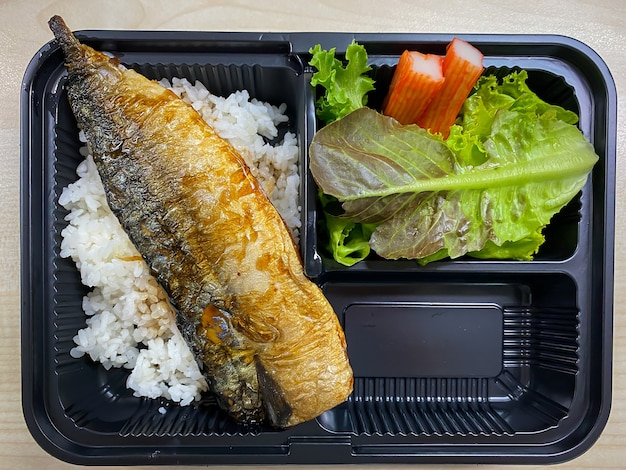 Saba fish grilled with teriyaki sauce on topped rice bowl in the plastic container