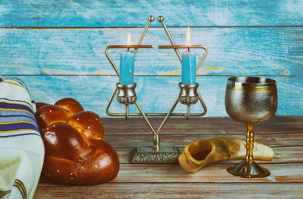 Sabbath jewish holiday challah bread and candelas on wooden table