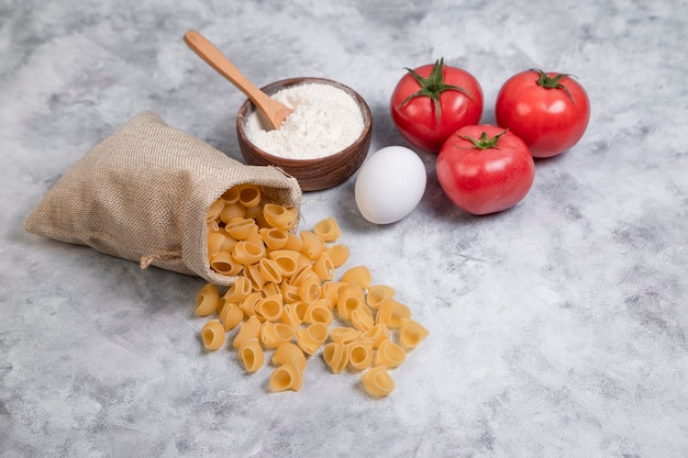 Sack bag of dried shell shaped macaroni with a wooden bowl of flour