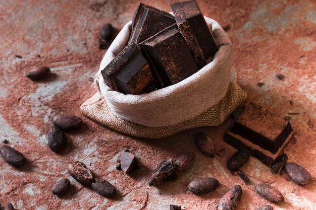 Sack of chocolate bar pieces and cocoa powder and beans on table