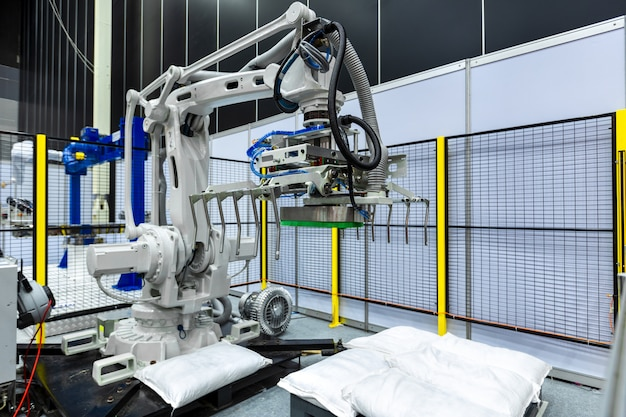 Sack gripper on industrial robot arm in production line manufacturer factory.