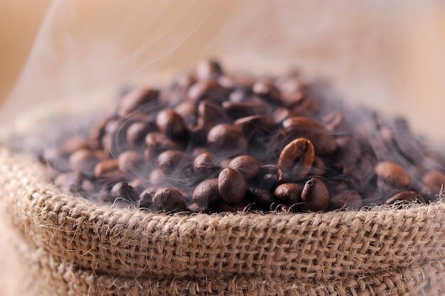 木製の背景にコーヒー豆の袋