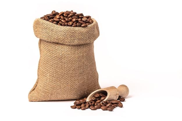Мешок с коричневыми обжаренными кофейными зернами. мешок из мешковины. совок с зернами. на белом фоне.