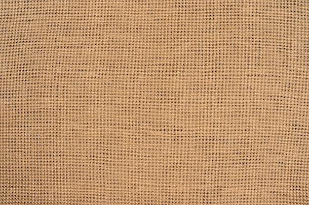 荒布黄麻布織りテクスチャ背景ベージュセピアブラウン色のオーガニックリネン生地テキスタイル