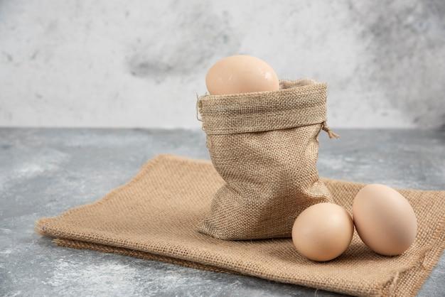 Вретище, полное органических свежих сырых яиц на мраморной поверхности.