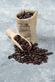 Sackcloth full of roasted coffee beans and wooden spoon on marble surface.
