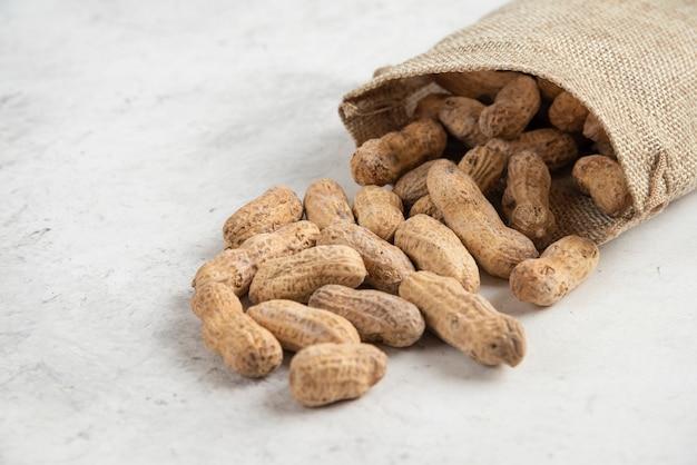 大理石のテーブルに置かれた天然のローストピーナッツの荒布。