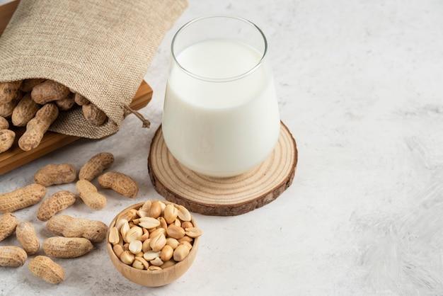 大理石のテーブルに有機ローストピーナッツとガラスミルクの荒布。