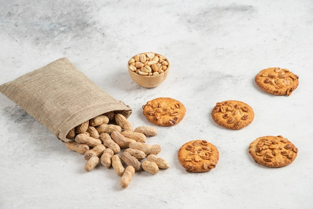 Sackcloth of organic peanuts and delicious biscuits on marble table.