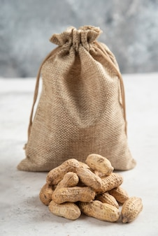 Sackcloth of organic roasted peanuts placed on marble table.