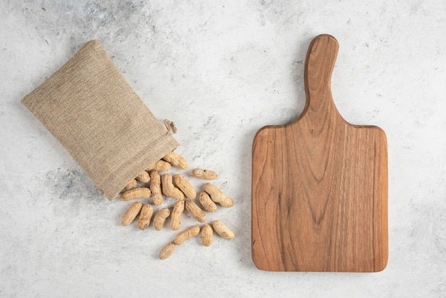 Sackcloth of organic roasted peanuts and wooden board on marble table.