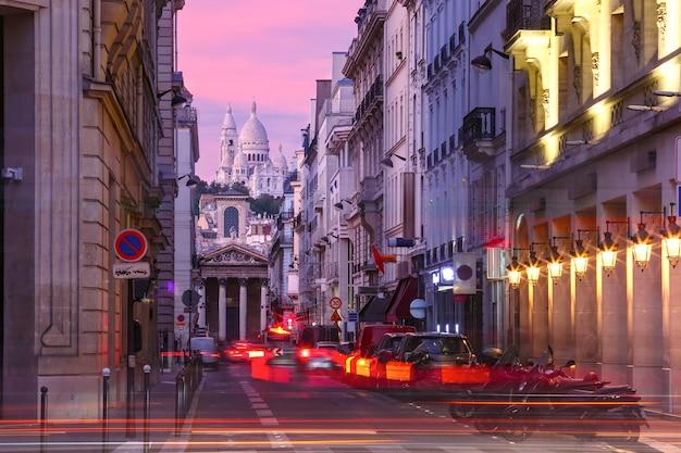 フランス、パリのラファイエット通りから見た、ピンクの夕日のサクレクール寺院とノートルダムドゥロレット教会