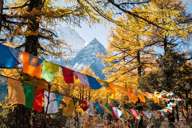 Sacred xiannairi mountain with colorful prayer flags blowing in autumn forest