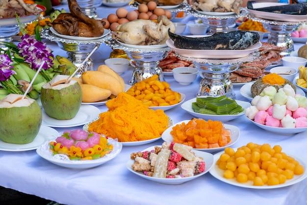 Жертвенное предложение пищи для молитвы богу и памятник предку, бангкок, таиланд. закройте вверх. традиционные подношения богам с едой, овощами и фруктами для богов тайской культуры