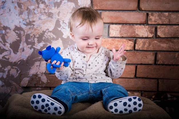 Грустный о мировых проблемах маленький ребенок сидит на железной бочке мальчик у кирпичной стены