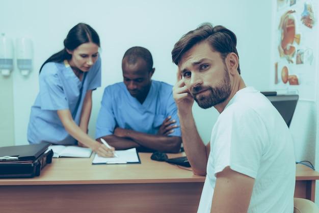 Sad adult caucasian man on reception at doctor