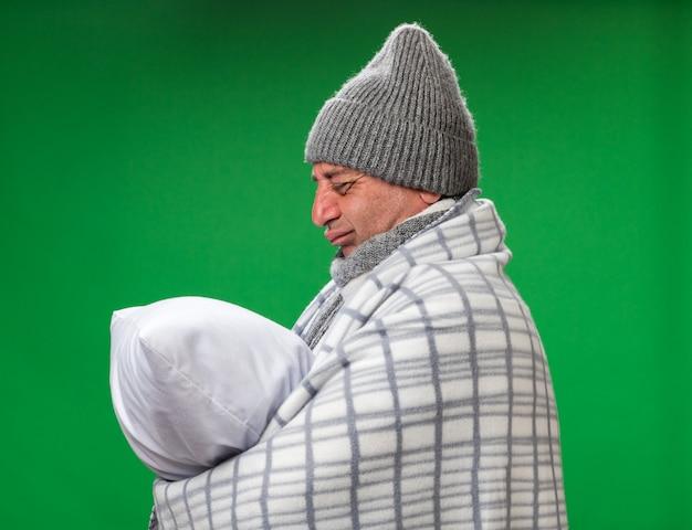 Грустный взрослый больной кавказский мужчина с шарфом на шее в зимней шапке, завернутый в плед, держит и смотрит на подушку, изолированную на зеленой стене с копией пространства