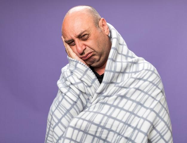格子縞に包まれた悲しい大人の病気の白人男性は、コピースペースで紫色の壁に隔離された顔に手を置きます
