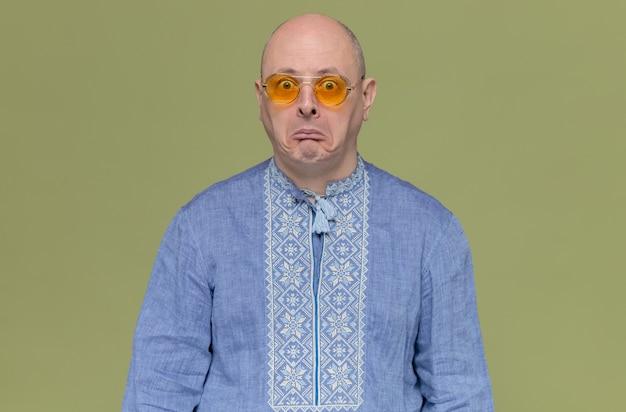 Грустный взрослый мужчина в синей рубашке в темных очках смотрит