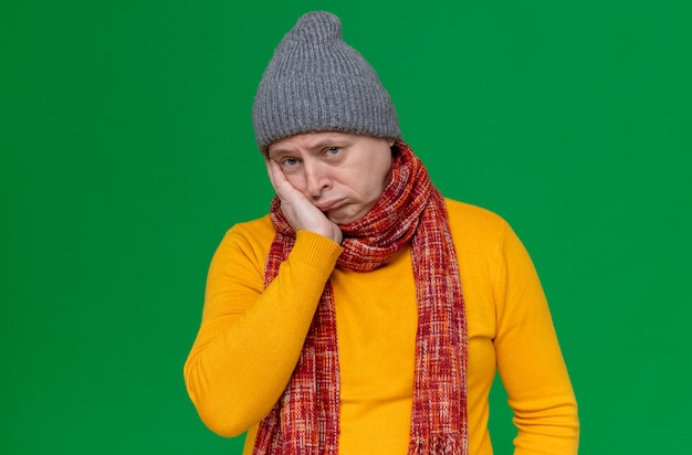 Sad adult man with winter hat and scarf around his neck putting hand on his face and looking