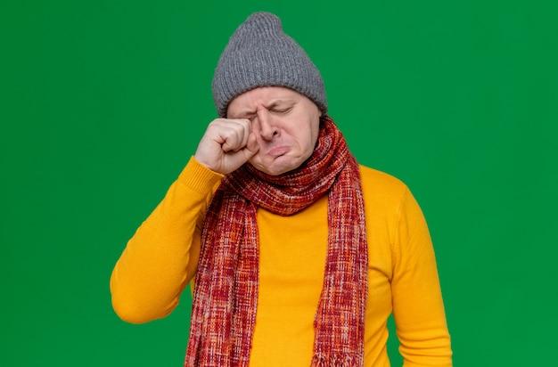 冬の帽子と首にスカーフを持った悲しい大人のスラブ人が手で涙を拭く