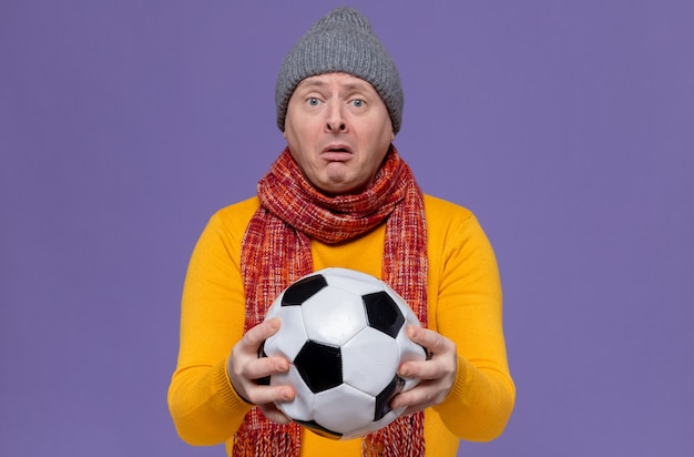 Sad adult slavic man with winter hat and scarf around his neck holding ball