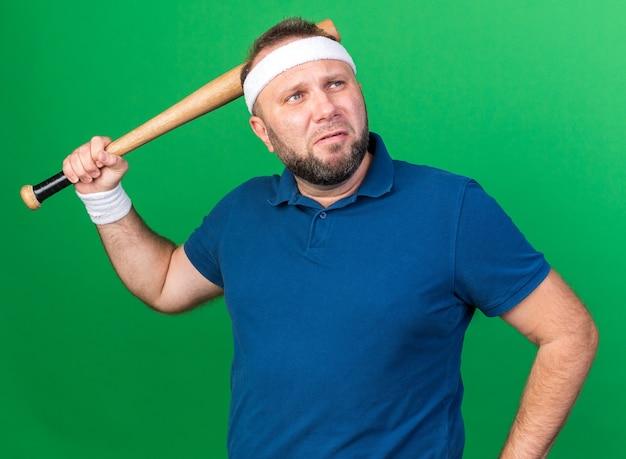 Грустный взрослый славянский спортивный мужчина с головной повязкой и браслетами держит летучую мышь и смотрит в сторону, изолированную на зеленой стене с копией пространства