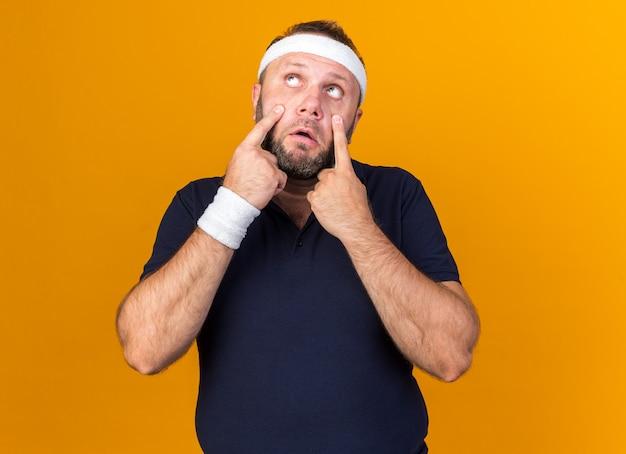 복사 공간 오렌지 벽에 고립 된 손가락으로 눈꺼풀을 당기는 머리띠와 팔찌를 착용 슬픈 성인 슬라브 스포티 한 남자