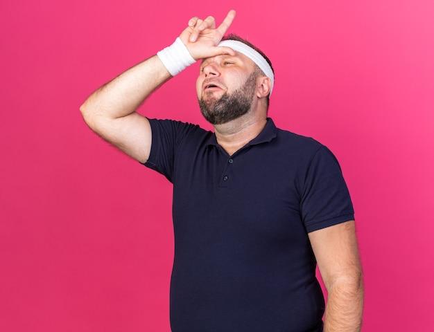 ヘッドバンドとリストバンドを身に着けている悲しい大人のスラブのスポーティな男は、コピースペースでピンクの壁に分離された額のジェスチャー敗者のサインに手を置く
