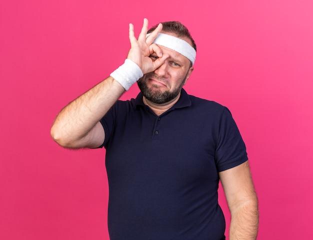 Грустный взрослый славянский спортивный мужчина с головной повязкой и браслетами сквозь пальцы, изолированные на розовой стене с копией пространства
