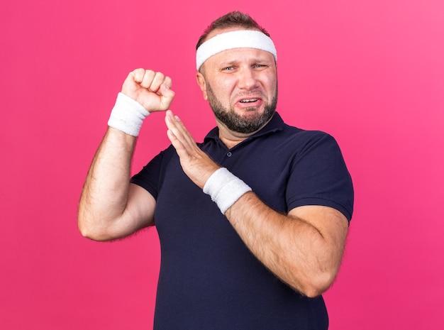 Triste adulto slavo sportivo da indossare fascia e braccialetti tenendo il pugno in alto e la mano aperta isolata sulla parete rosa con spazio di copia