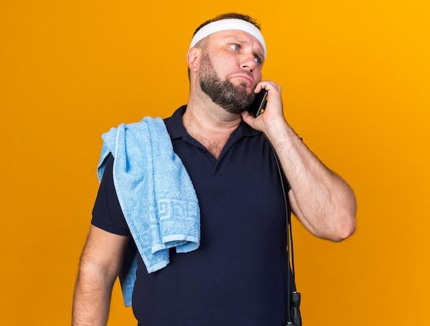 Uomo sportivo slavo adulto triste con corda per saltare intorno al collo e asciugamano sulla spalla che indossa fascia e braccialetti parlando al telefono isolato sulla parete arancione con spazio di copia