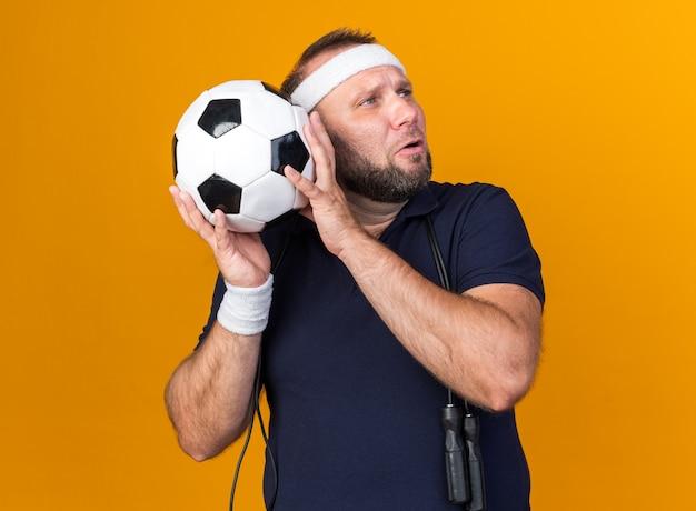 Грустный взрослый славянский спортивный мужчина со скакалкой на шее в головной повязке и браслетах держит мяч и смотрит в сторону, изолированную на оранжевой стене с копией пространства