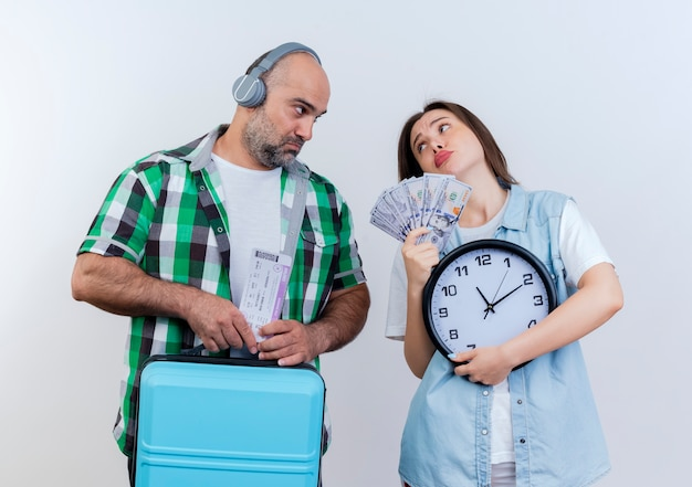 旅行のチケットを保持しているヘッドフォンを身に着けている悲しい大人の旅行者のカップルの男性とお金と時計を保持しているスーツケースの女性がお互いを見て