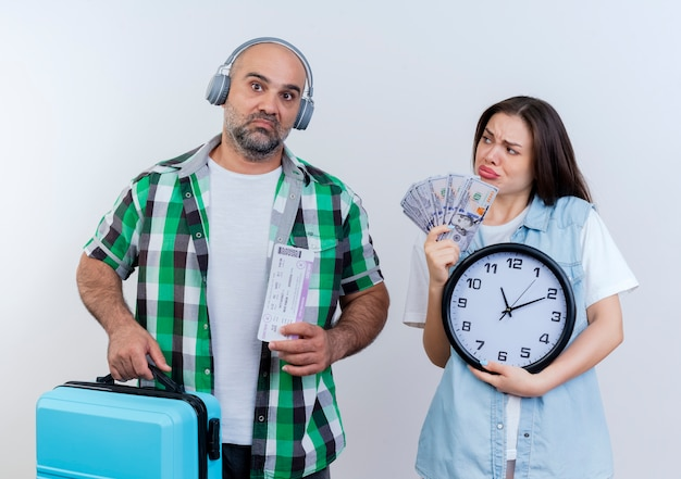 Sad adult traveler couple man wearing headphones holding travel tickets and suitcase looking woman holding money and clock looking at him