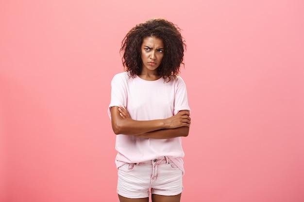 ピンクの壁を見ている眉をひそめている悲しいアフリカ系アメリカ人の女性の交差腕