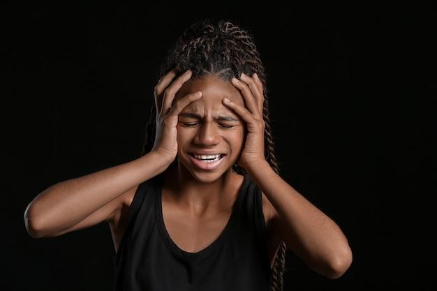 Грустная афро-американская девушка, изолированная на темноте
