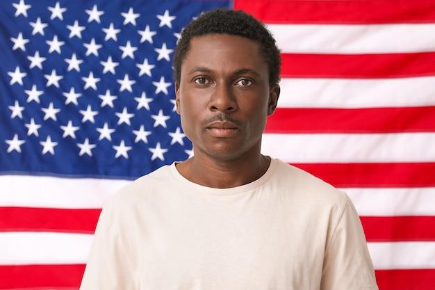 미국 국기 근처 슬픈 아프리카 계 미국인 남자. 인종 차별 중지