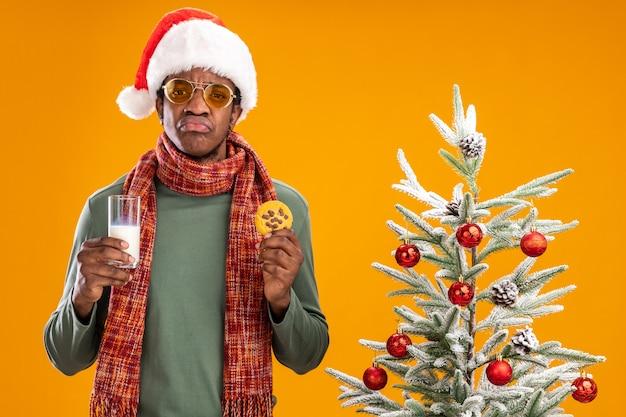 Triste uomo afroamericano in santa cappello e sciarpa intorno al collo tenendo un bicchiere di latte e cookie pursing labbra in piedi accanto a un albero di natale su sfondo arancione