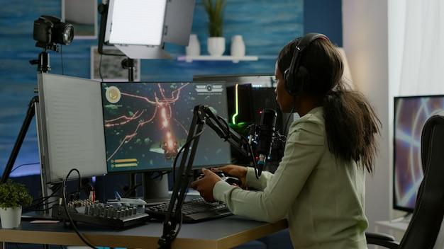 조이패드를 들고 헤드폰을 끼고 얼굴을 덮는 온라인 경쟁에서 지고 슬픈 아프리카 e 스포츠 스트리밍. rgb 강력한 컴퓨터에서 새로운 그래픽으로 온라인 비디오 게임을 스트리밍하는 프로 게이머.