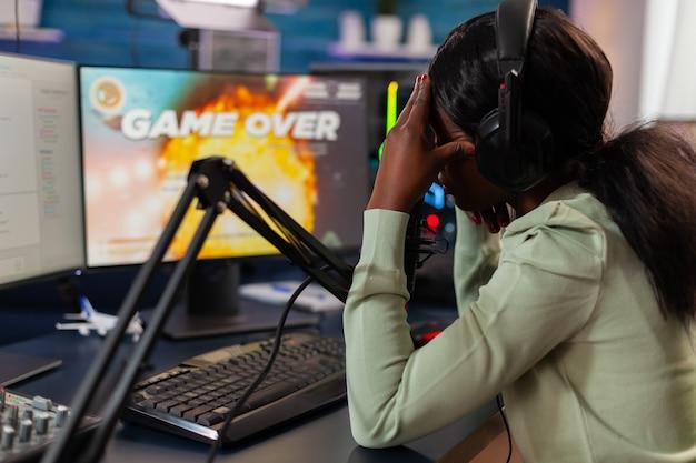 헤드폰을 끼고 얼굴을 가리는 온라인 경쟁에서 지고 슬픈 아프리카 e 스포츠 스트리밍. 강력한 컴퓨터에서 새로운 그래픽으로 온라인 비디오 게임을 스트리밍하는 전문 게이머.