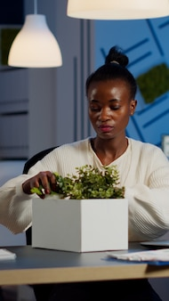 Sad african fired businesswoman packing things in box