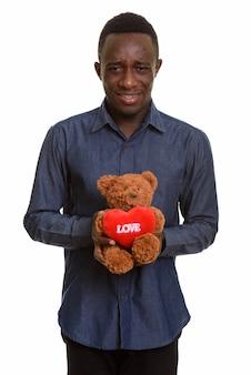 Грустный африканский мужчина держит плюшевого мишку с сердцем и знаком любви