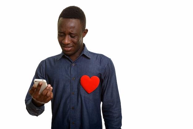 Грустный африканский мужчина с красным сердцем на груди с помощью мобильного телефона